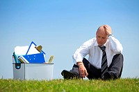 Cheerless businessman sitting next to basket full of files in park