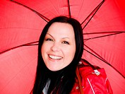 smiling brunette woman in fall, rainproof clothes holding umbrel