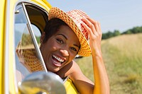 Smiling mixed race woman leaning out of car window