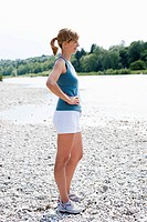 Germany, Munich, Mid adult woman standing near Isar river, smiling