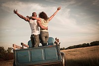 Couple standing together in back of old_fashioned truck