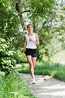 Germany, Munich, Mid adult woman jogging along Isar river, portrait