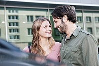 Germany, Cologne, Young couple near car, smiling