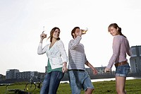 Germany, Cologne, Young man and woman dancing with beer bottles, smiling