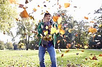 Germany, Cologne, Young man playing with leaves in park, smiling, portrait