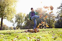 Germany, Cologne, Young man playing with leaves in park, smiling