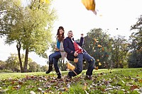 Germany, Cologne, Couple playing in park, smiling, portrait