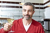 Germany, Cologne, Mature man drinking wine, smiling, portrait