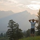 Man looks out from mountain meadow, sunrise
