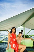 Couple riding in boat on tropical waters