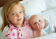 Girl hugging infant sibling in bed