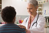 Doctor talking to boy in doctor´s office