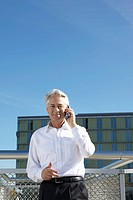 Germany, Bavaria, Munich,Businessman talking on phone, smiling, portrait