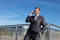 Germany, Bavaria, Munich,Businessman talking on cell phone, smiling