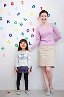 A woman and girl with alphabet blocks on the wall