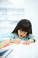 A girl writing on a notebook with a pencil