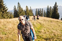 Man hiking with pack on grassy hillside
