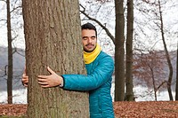 Germany, Berlin, Wandlitz, Young man hugging tree