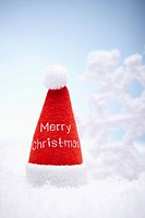 A red Santa Clause hat and white snowflake on the snow