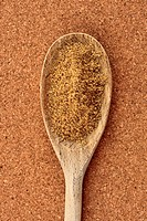 Ground coriander on a wooden spoon close up on a cork background