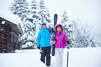 Couple carrying skis and poles in snow