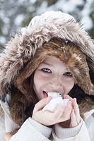 Teenage girl licking snowball