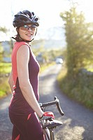 Cyclist standing on rural road