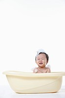 A baby taking a bath in the bathtub with the bubble on his body
