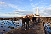 England, Northumberland, Whitley Bay. People walking across the concrete causeway to St Mary´s Lighthouse near Whitley Bay.