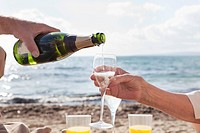 Spain, Mallorca, Senior couple drinking sparkling wine at beach