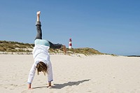 Woman turning cartwheels on sandy beach, Ellenbogen, List, Sylt, Schleswig_Holstein, Germany