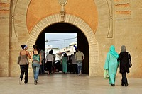 Moroccan women dressed in modern clothes and traditional clothes in front of the gate to medina, Rabat, Morocco