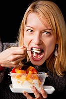 Woman eating yoghurt with fruit