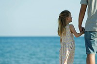 Girl holding her father´s hand at the beach, cropped