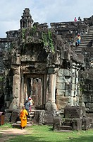 Buddhist monk and visitors at the entrance tower of Bakong Temple, Roluos Group, Angkor, Siem Reap, Cambodia, Southeast Asia, Asia