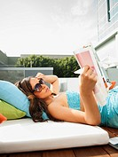 Mixed race woman sunbathing and reading magazine