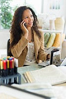 Hispanic businesswoman using cell phone at desk