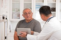 Doctor using digital tablet to talk to senior man
