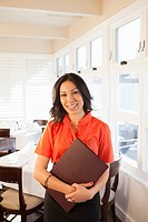 Mixed race hostess holding menus in restaurant