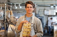 Caucasian baker holding cookies in bakery