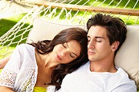 Couple napping together in hammock
