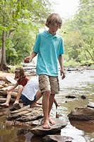 Caucasian children playing near stream