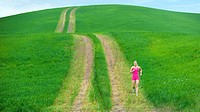 Caucasian woman running on path through field