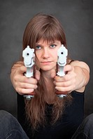 Young serious woman aims from two pistols