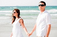 Young couple holding hands and walking by the beach