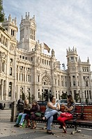 People sitting in front of Communication's Palace in Madrid, Spain