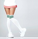 Low section of woman wearing sneakers and knee_high socks