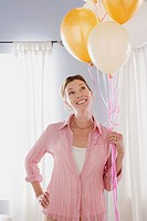 Smiling mature woman holding balloons