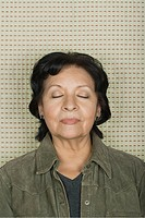 Studio portrait of senior woman with eyes closed