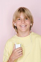 Studio shot portrait of teenage boy with mp3 player, head and shoulders